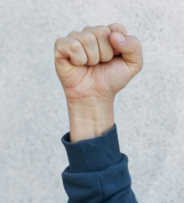 Unknown person protesting, activist fist up during strike. Activism for equal human rights or against racism, faceless human upraising fist isolated over white background.